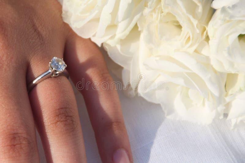 Ένα κομψό δαχτυλίδι διαμαντιών δέσμευσης σε ετοιμότητα γυναικών ` s και μια ανθοδέσμη άσπρου Lisianthus ανθίζει στοκ εικόνες