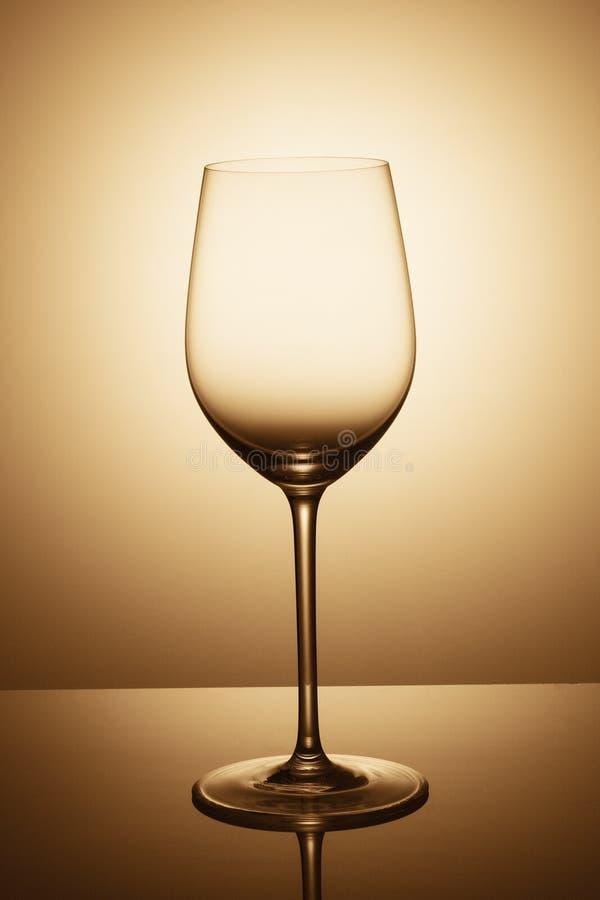 Ένα κομψό κενό ποτήρι του κρασιού στέκεται απέναντι από το φως στοκ εικόνες