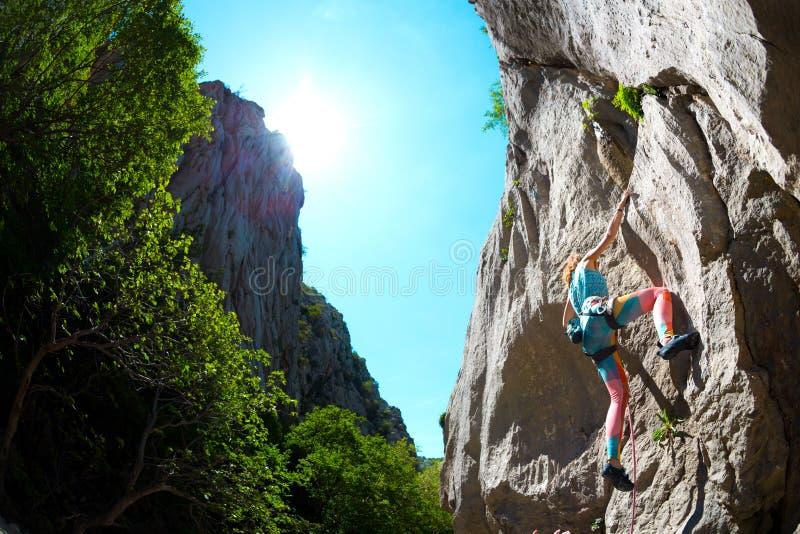 Ένα κορίτσι αναρριχείται σε έναν βράχο στοκ εικόνες