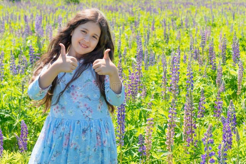 Ένα κορίτσι αντίχειρες στους πορφυρούς φορεμάτων επάνω, που χαμογελούν και που εξετάζουν τη κάμερα o r στοκ εικόνες