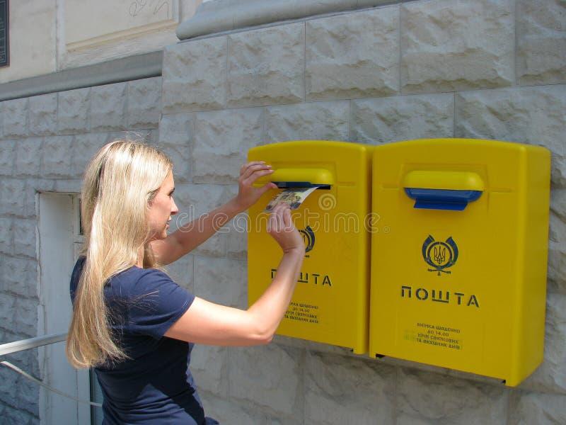 Ένα κορίτσι βάζει μια κάρτα σε ένα μετα κιβώτιο στοκ φωτογραφίες με δικαίωμα ελεύθερης χρήσης