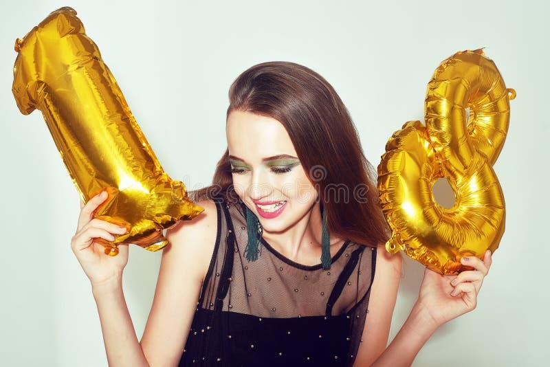 Ένα κορίτσι γενεθλίων στα 18α γενέθλιά της με το χρυσό αριθμό baloons Το συγκινημένο κορίτσι δεκαοχτώ με πράσινο κάνει το επάνω κ στοκ φωτογραφία με δικαίωμα ελεύθερης χρήσης