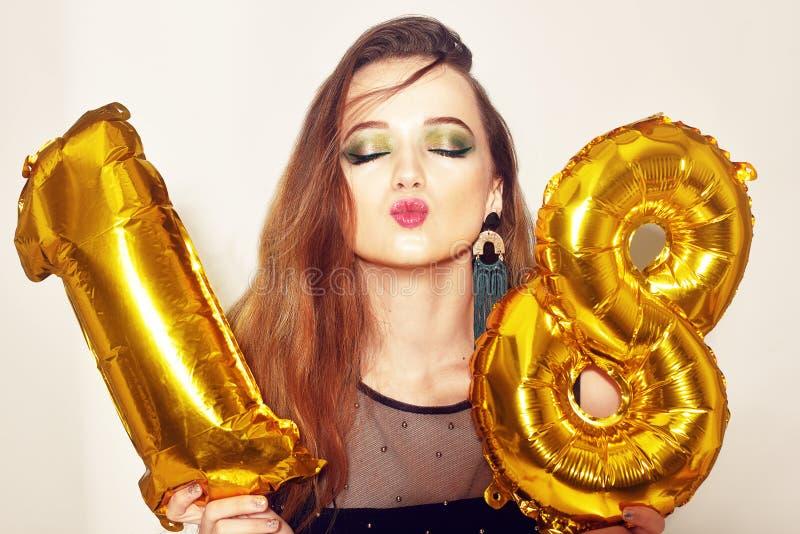 Ένα κορίτσι γενεθλίων στα 18α γενέθλιά της με το χρυσό αριθμό baloons Το συγκινημένο κορίτσι δεκαοχτώ με πράσινο κάνει το επάνω κ στοκ φωτογραφίες με δικαίωμα ελεύθερης χρήσης