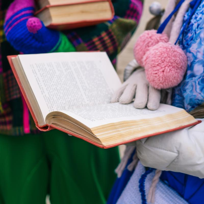 Ένα κορίτσι διαβάζει ένα βιβλίο Ανοιγμένο βιβλίο στα χέρια μιας νέας γυναίκας Εκπαιδευτική διαδικασία Διάλεξη για τους σπουδαστές στοκ εικόνες