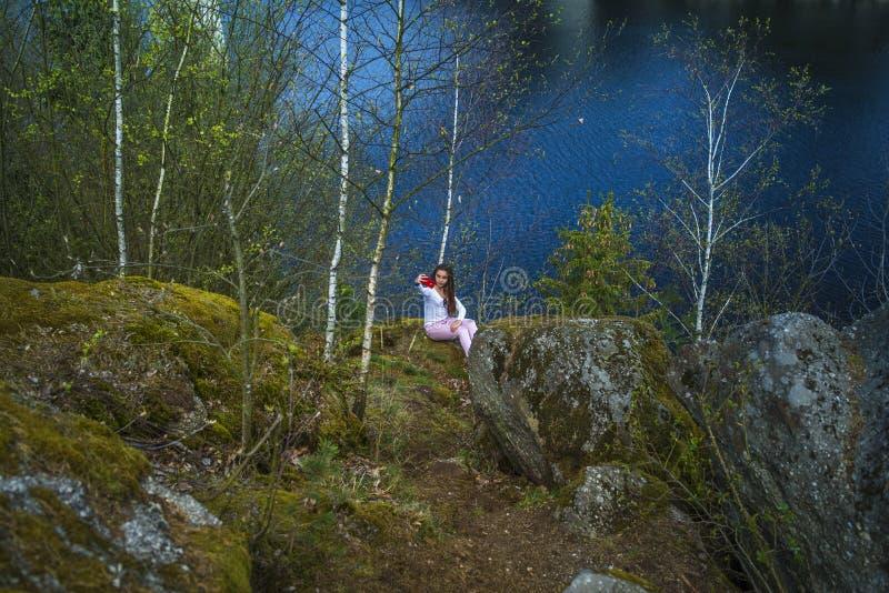 Ένα κορίτσι κάθεται σε έναν απότομο βράχο και εξετάζει τη φύση, τη συνεδρίαση κοριτσιών σε έναν βράχο και την απόλαυση της θέας κ στοκ φωτογραφία με δικαίωμα ελεύθερης χρήσης