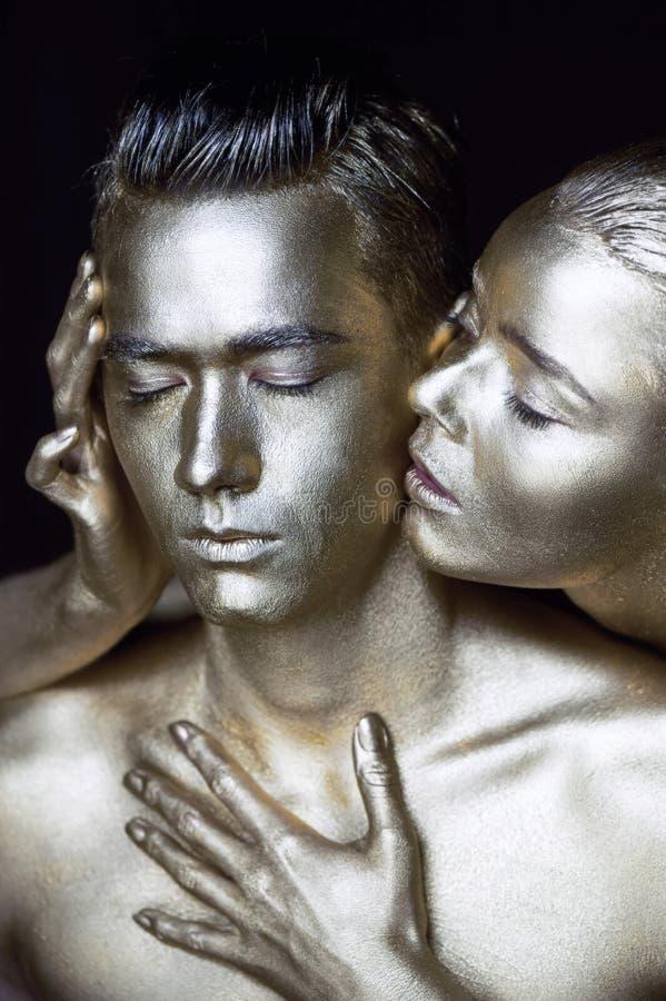 Ένα κορίτσι και ένας τύπος που καλύπτονται στο ασημένιο χρώμα Με τις προσοχές μου ιδιαίτερες Το κορίτσι έκλινε μέσα και φιλά το α στοκ εικόνες
