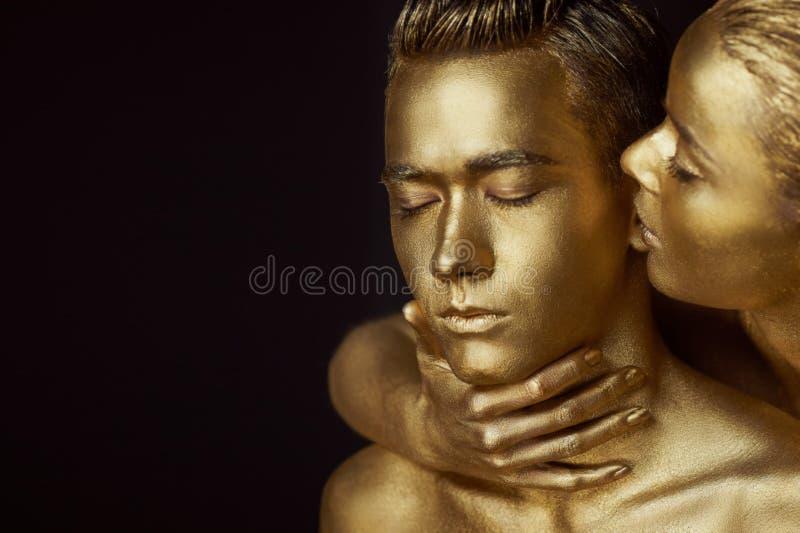 Ένα κορίτσι και ένας τύπος που καλύπτονται στο χρυσό χρώμα Με τις προσοχές μου ιδιαίτερες Το κορίτσι έκλινε μέσα και φιλά το αυτί στοκ εικόνα