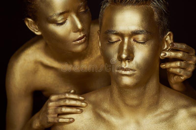 Ένα κορίτσι και ένας τύπος που καλύπτονται στο χρυσό χρώμα Με τις προσοχές μου ιδιαίτερες Το κορίτσι που κλίνεται στοκ φωτογραφίες με δικαίωμα ελεύθερης χρήσης