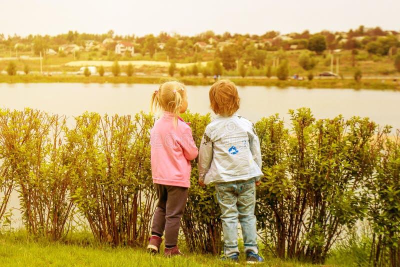Ένα κορίτσι και ένα αγόρι που εξετάζουν σε μια άλλες όχθεις του ποταμού ένα ηλιοβασίλεμα στοκ εικόνα