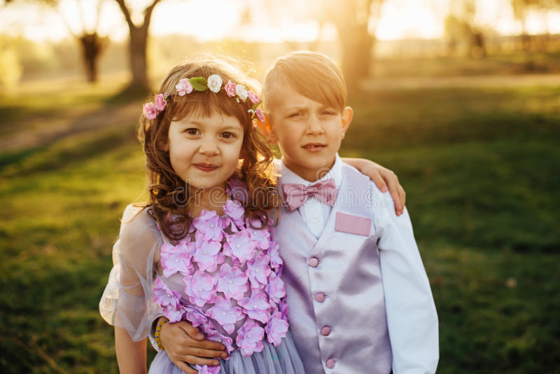 Ένα κορίτσι και ένα αγόρι στα έξυπνα ενδύματα περπατούν στο πάρκο στοκ εικόνες