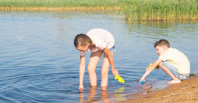 Ένα κορίτσι και ένα αγόρι συλλέγουν το νερό από μια λίμνη στα πυροβόλα όπλα νερού για να παίξουν σε τους, ενάντια στο σκηνικό του στοκ φωτογραφία