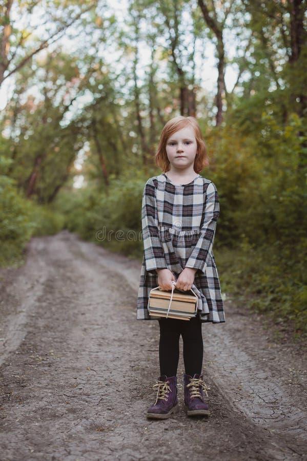 Ένα κορίτσι κρατά έναν σωρό του βιβλίου στεμένος στο δρόμο στοκ φωτογραφία