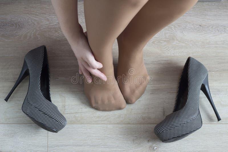 Ένα κορίτσι κρατά επάνω στο πόδι της, κούραση από το πρότυπο τακουνιών της στοκ εικόνες