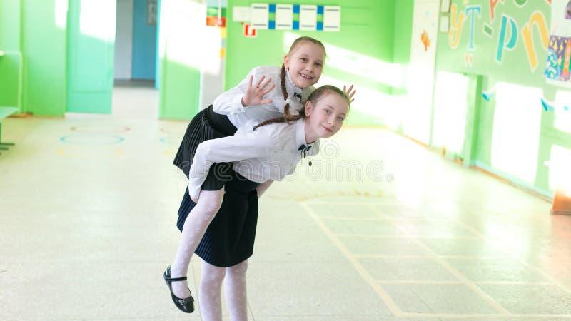 Ένα κορίτσι μαθητριών φύτεψε τη νεώτερη αδελφή της σε την πίσω στοκ εικόνα