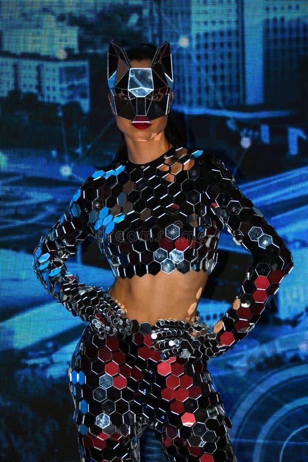 Ένα κορίτσι με έναν λεπτό αριθμό σε ένα φανταστικό κοστούμι καθρεφτών με μια μάσκα των καθρεφτών που αποδίδουν στο χώρο στοκ φωτογραφία με δικαίωμα ελεύθερης χρήσης