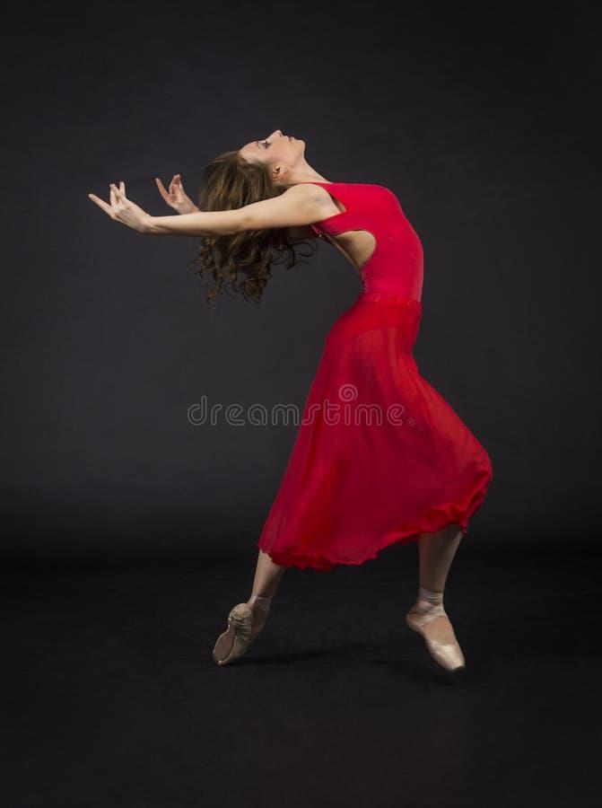 Ένα κορίτσι με μακρυμάλλη, στο κόκκινο, μπαλέτο χορού στοκ εικόνα