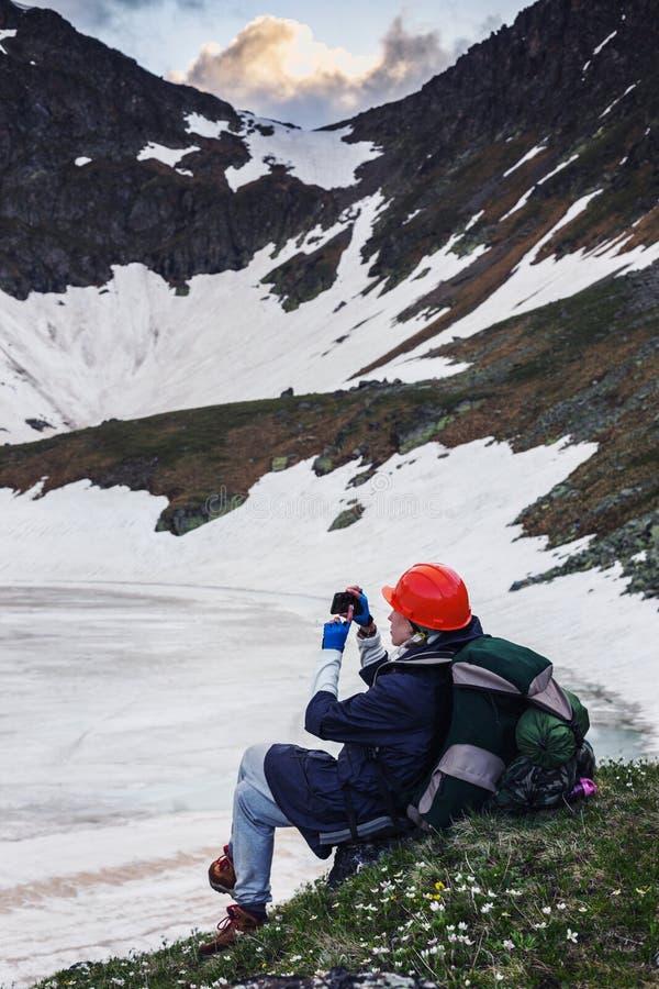 Ένα κορίτσι με ένα σακίδιο πλάτης φωτογραφίζεται χρησιμοποιώντας το smartphone της στοκ εικόνα με δικαίωμα ελεύθερης χρήσης