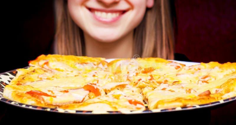 Ένα κορίτσι με ένα συμπαθητικό χαμόγελο κρατά μια φρέσκια πίτσα στο tray_ στοκ εικόνες