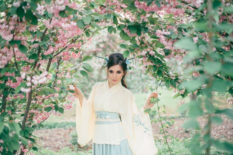 Ένα κορίτσι με τη μακριά, μαύρη τρίχα διακόσμησε με Kandzashi, τα λουλούδια και τις μακριές καρφίτσες με τις χάντρες κρυστάλλου Γ στοκ εικόνες