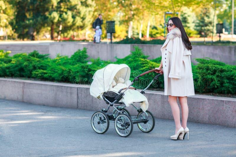 Ένα κορίτσι με τους σκοτεινούς μακρυμάλλεις περιπάτους με ένα μωρό στο πάρκο στοκ εικόνα