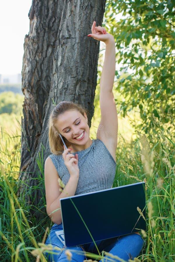 Ένα κορίτσι με ένα lap-top είναι ευχαριστημένο από την επιτυχία στην επιχείρησή της στοκ εικόνες