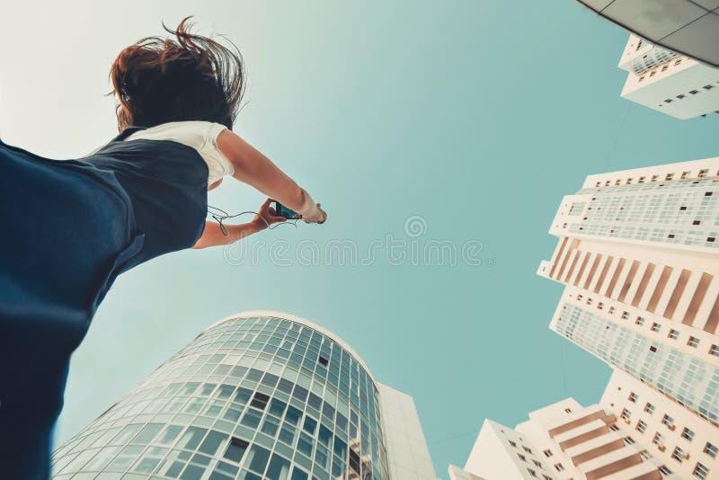 Ένα κορίτσι παίρνει τις εικόνες νέου κατοικημένου ενός σύνθετου Άσπροι σύγχρονοι ουρανοξύστες Νέα οικοδόμηση στοκ φωτογραφία