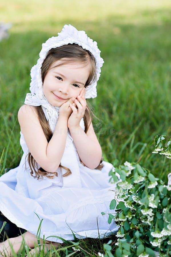 Ένα κορίτσι ποιμένων σε ένα άσπρα φόρεμα και ένα καπό ταΐζει μια αίγα με τα φύλλα λάχανων στοκ φωτογραφίες με δικαίωμα ελεύθερης χρήσης