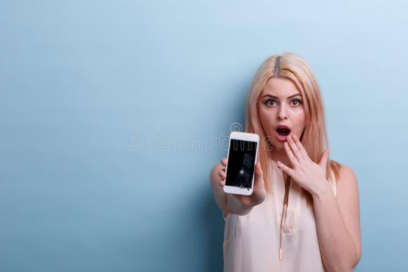 Ένα κορίτσι πολύ έκπληκτο παρουσιάζει ότι ένα σπασμένο τηλέφωνο το χέρι σε ένα μπλε υπόβαθρο στοκ εικόνα με δικαίωμα ελεύθερης χρήσης