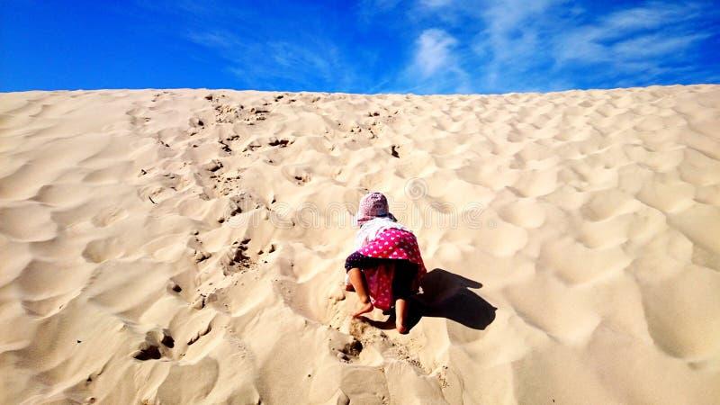 Ένα κορίτσι που αναρριχείται σε έναν λόφο ερήμων στοκ εικόνα