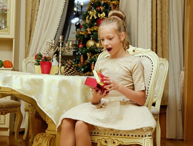 Ένα κορίτσι που ανοίγει ένα κιβώτιο δώρων στα Χριστούγεννα στοκ εικόνα