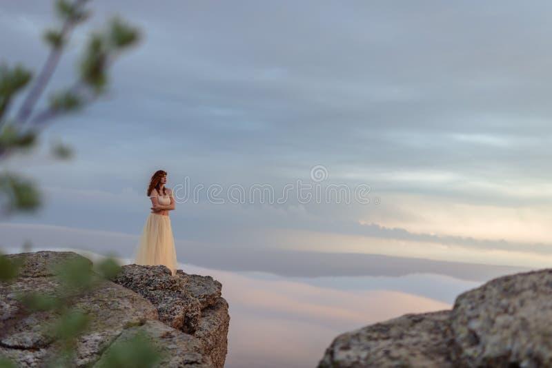 Ένα κορίτσι που θαυμάζει την αυγή ή το ηλιοβασίλεμα του ήλιου σε μια γραφική θέση στα βουνά στοκ φωτογραφία με δικαίωμα ελεύθερης χρήσης