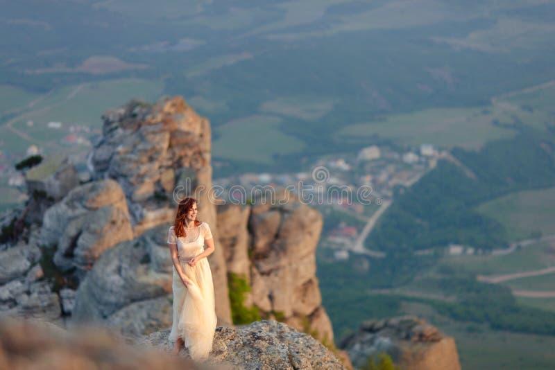 Ένα κορίτσι που θαυμάζει την αυγή ή το ηλιοβασίλεμα του ήλιου σε μια γραφική θέση στα βουνά στοκ εικόνες