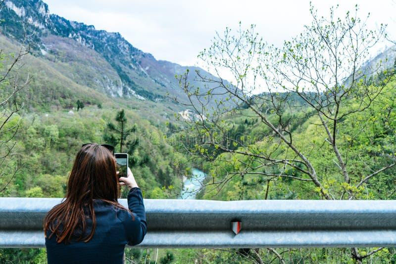 Ένα κορίτσι που στέκεται στον απότομο βράχο και που παίρνει τη φωτογραφία της κοιλάδας με τον ποταμό Κόκκινη επικεφαλής κάνοντας  στοκ εικόνα