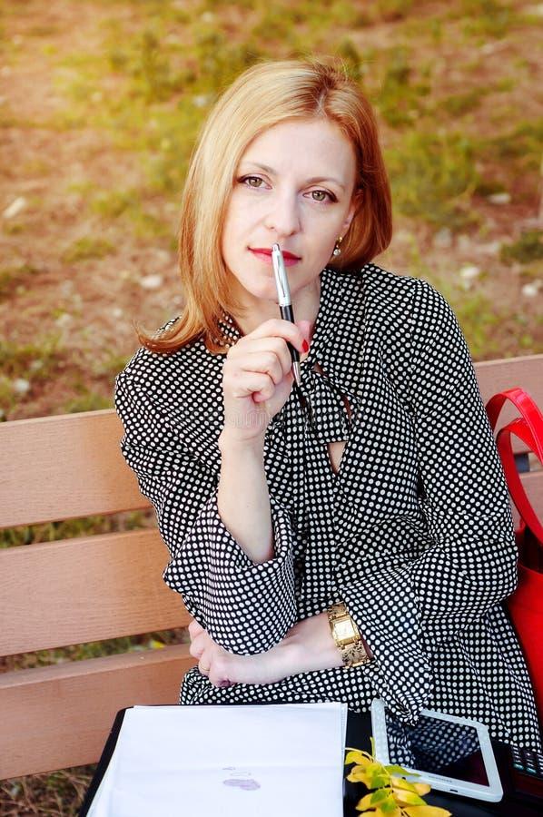 Ένα κορίτσι που στηρίζεται σε ένα πάρκο, στην ώρα μεσημεριανού γεύματος Μια γυναίκα ερωτευμένη Η γυναίκα σκέφτεται τι για να γράψ στοκ εικόνες