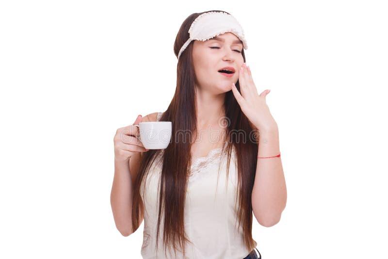 Ένα κορίτσι που φορά μια μάσκα για τον ύπνο, χασμουρητά που καλύπτει το στόμα με το χέρι και που κρατά ένα φλιτζάνι του καφέ στοκ εικόνα με δικαίωμα ελεύθερης χρήσης