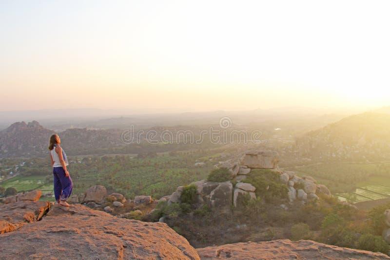 Ένα κορίτσι προσέχει το ηλιοβασίλεμα σε Hampi Το κορίτσι στέκεται πάνω από το βουνό και εξετάζει την απόσταση Περισυλλογή, αρμονί στοκ εικόνα με δικαίωμα ελεύθερης χρήσης