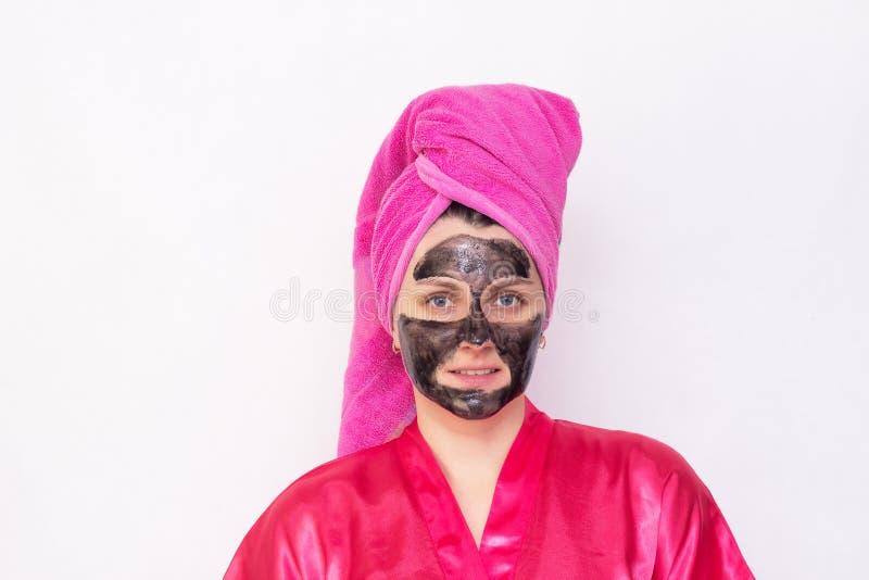 Ένα κορίτσι σε ένα άσπρο υπόβαθρο με μια μαύρη μάσκα στο πρόσωπό της ενάντια στα σπυράκια και τα μαύρα σημεία σε μια ρόδινη τήβεν στοκ εικόνες με δικαίωμα ελεύθερης χρήσης