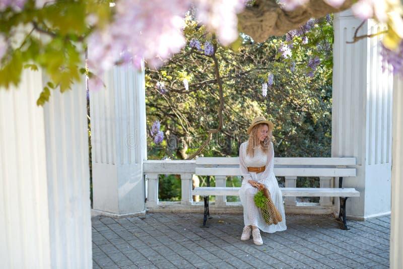Ένα κορίτσι σε ένα άσπρο φόρεμα και ένα καπέλο αχύρου απολαμβάνει το άνθισμα του wisteria στοκ φωτογραφία