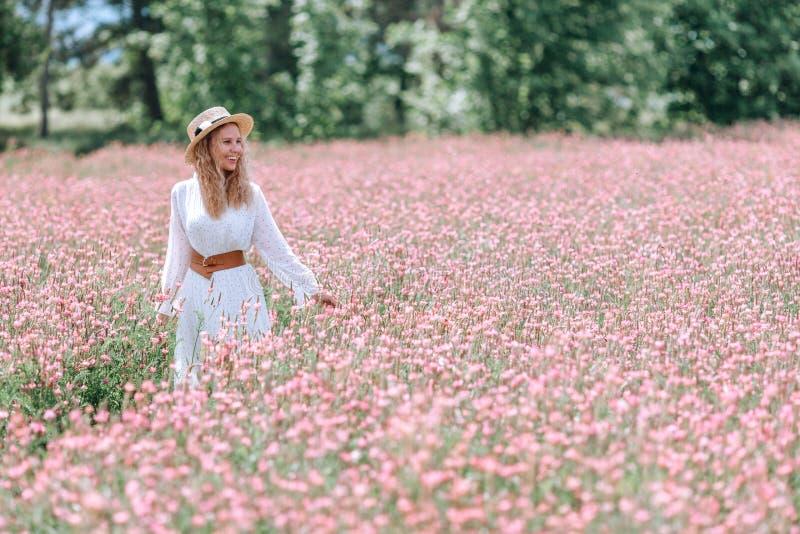 Ένα κορίτσι σε ένα άσπρο φόρεμα με τα σημεία Πόλκα και ένα καπέλο σε έναν ανθίζοντας τομέα sainfoin στοκ εικόνες