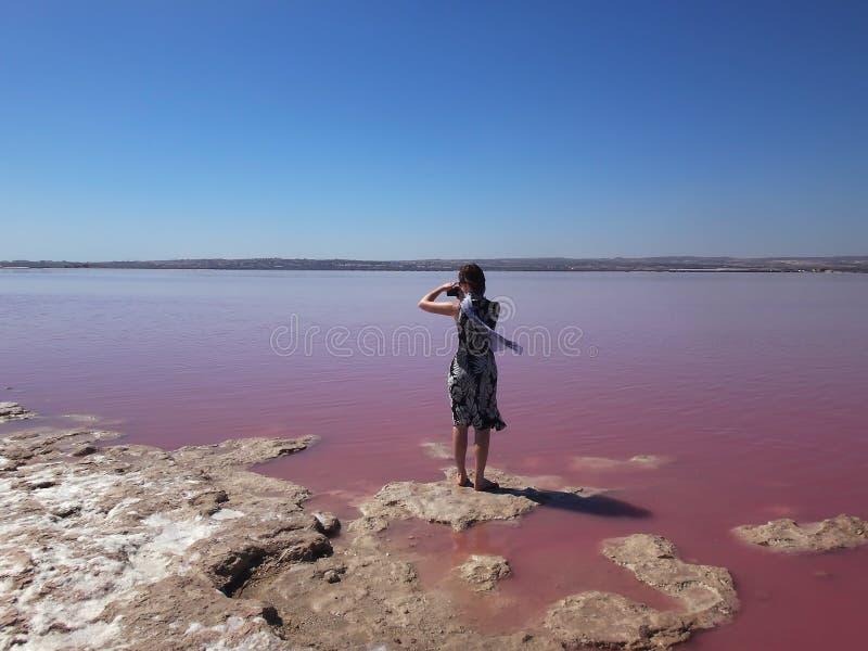 Ένα κορίτσι σε ένα ελαφρύ μαντίλι φορεμάτων και μεταξιού φωτογραφίζει μια ρόδινη λίμνη Torrevieja, Ισπανία στοκ εικόνα με δικαίωμα ελεύθερης χρήσης