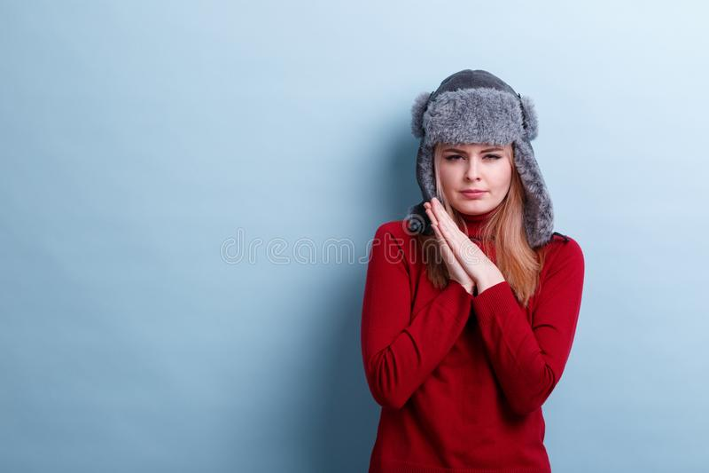 Ένα κορίτσι σε ένα θερμά καπέλο και ένα πουλόβερ γουνών, έβαλε τα χέρια μαζί και επαρέκκλινε τα μάτια για να παρουσιάσει το κρύο στοκ εικόνες