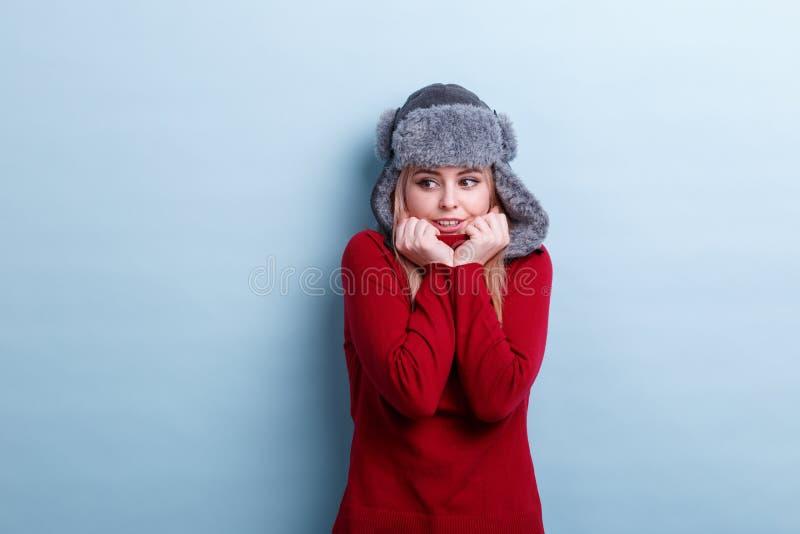 Ένα κορίτσι σε ένα θερμά καπέλο και ένα πουλόβερ, διατηρεί το λαιμό του πουλόβερ καταδεικνύοντας το κρύο στοκ εικόνες