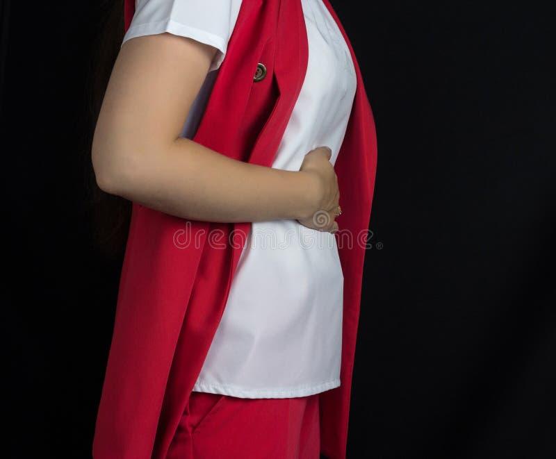 Ένα κορίτσι σε ένα κόκκινο κοστούμι διατηρεί το στομάχι της, πόνος στομαχιών, μαύρο υπόβαθρο στοκ εικόνες