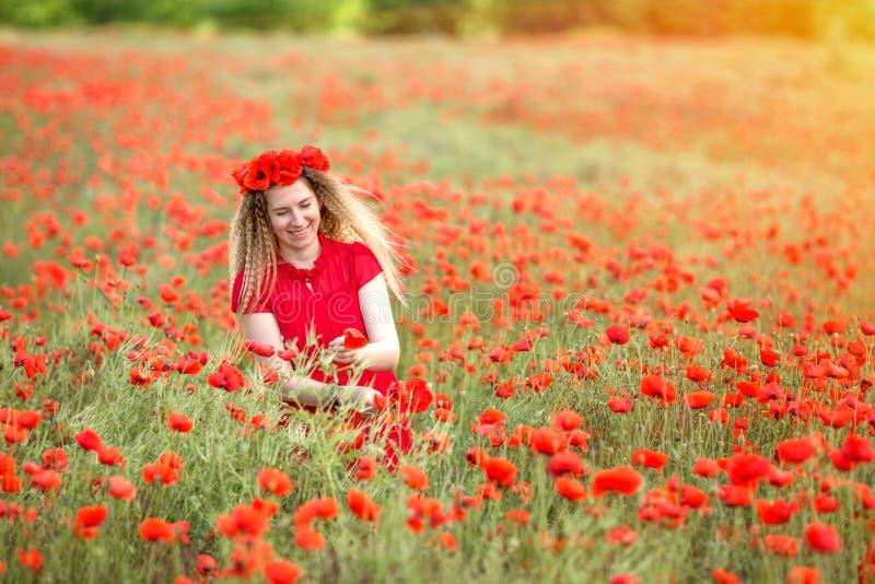 Ένα κορίτσι σε ένα κόκκινο φόρεμα υφαίνει τα στεφάνια των λουλουδιών παπαρουνών σε έναν τομέα παπαρουνών στοκ φωτογραφίες