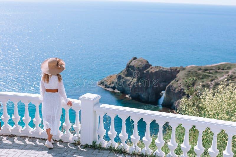 Ένα κορίτσι σε ένα λευκό σαν το χιόνι φόρεμα και ένα καπέλο με έναν ευρύ χείλο θαυμάζει την άποψη της θάλασσας και των βράχων στοκ εικόνα