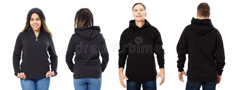 Ένα κορίτσι σε μια μαύρη μπλούζα με μια κουκούλα και ένα άτομο σε ένα μέτωπο και μια πλάτη μπλουζών που απομονώνονται, hoodie πρό στοκ φωτογραφία