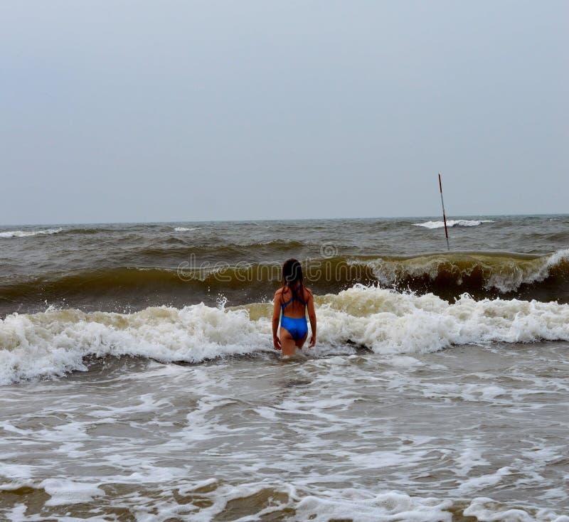 Ένα κορίτσι σε ένα μπλε μαγιό στην κίτρινη θάλασσα στοκ φωτογραφίες