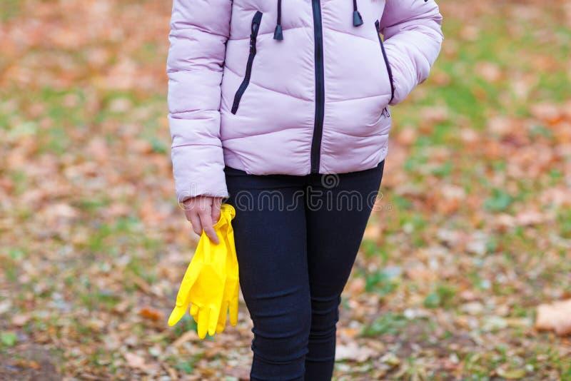 Ένα κορίτσι σε ένα πάρκο φθινοπώρου στέκεται με τα λαστιχένια γάντια, για τη συγκομιδή των φύλλων στοκ εικόνα