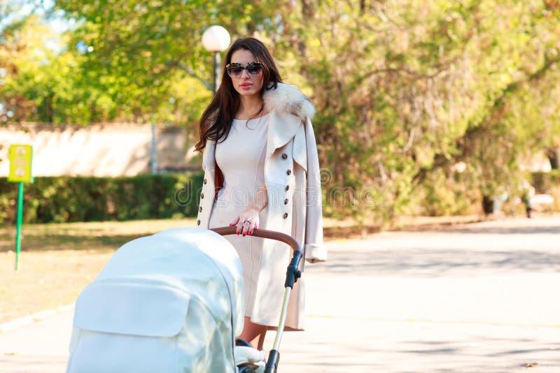 Ένα κορίτσι σε ένα παλτό και τα γυαλιά κυλά μια μεταφορά μωρών στην οδό στοκ εικόνες