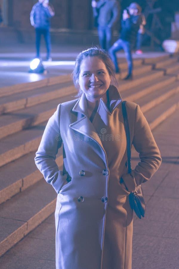 Ένα κορίτσι σε ένα παλτό περπατά μέσω των οδών νύχτας της πόλης κοντά στις προθήκες στοκ φωτογραφίες με δικαίωμα ελεύθερης χρήσης
